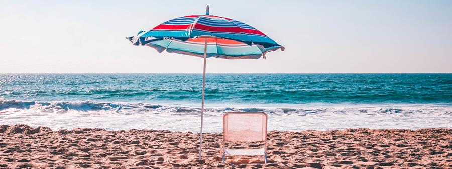 Umbrella next to an empty chair on the beach