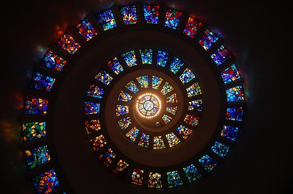 A photo of a glass spiral ceiling with stained glass.