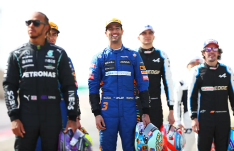 Formula One drivers standing and smiling while holding helmets