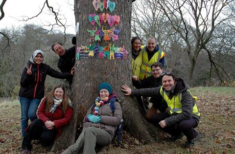 A group of Permaculture Association members at a local gathering in Sunderland. The tree is decorated by participants, with 'Fair Share. Future generations'